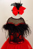 Dress has bodice with sweetheart neck polka dots & black mesh covered with crystals & feather trim. Skirt is red tricot with black satin hem. Has hair accessory. Front zoomed