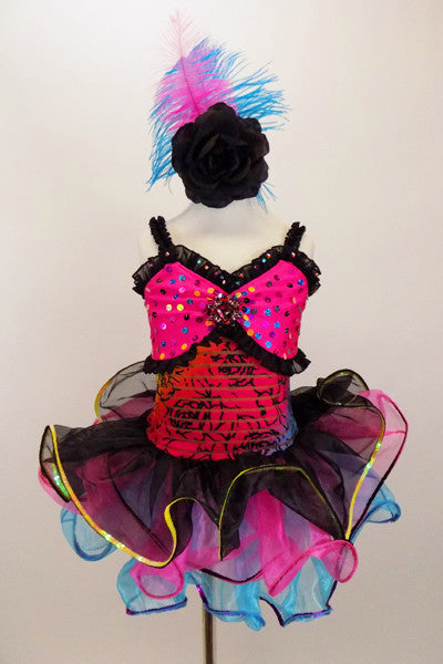 Dress has pink bust area with coloured sequins-crystals, black ruffles on sheer striped bodice & black rose pattern. Skirt is colourful curly hem ruffles. Comes with black rose & feather hair accessory and black gloves Front