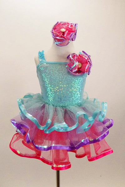 Pale aqua sequined dress has ruffled straps & pink-purple floral accent at left shoulder. Skirt has 3 tiers of pastel ruffles & matching hair accessory. Front