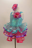 Pale aqua sequined dress has ruffled straps & pink-purple floral accent at left shoulder. Skirt has 3 tiers of pastel ruffles & matching hair accessory. Left side
