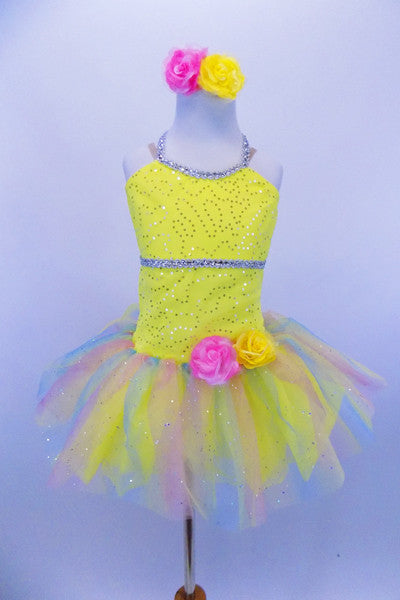 Sequin mesh overlays front bodice of  camisole leotard with silver braid trim. Rainbow sparkle tulle rests on yellow tricot tutu. Roses accent waist and hair. Front