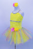 Sequin mesh overlays front bodice of  camisole leotard with silver braid trim. Rainbow sparkle tulle rests on yellow tricot tutu. Roses accent waist and hair. Left side