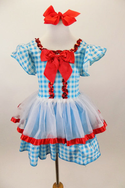 Blue & white check dress has ruffle sleeves, large red bow & sequin accent. Skirt has white sheer over-skirt with red satin edge. Comes with red ribbon hair bow. Front