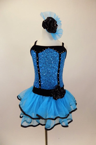 Blue sequin leotard has black velvet accents with crystals. Black satin rosettes accent the waist & hair accessory. Has ruffle layer skirt with black trim. Front