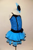 Blue sequin leotard has black velvet accents with crystals. Black satin rosettes accent the waist & hair accessory. Has ruffle layer skirt with black trim. Right side
