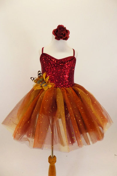 Rich earth-tone tutu dress has burgundy sequined bodice. Skirt is glitter ombré tulle over burgundy tulle layers with gold floral accent & hair accessory. Front