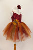 Rich earth-tone tutu dress has burgundy sequined bodice. Skirt is glitter ombré tulle over burgundy tulle layers with gold floral accent & hair accessory.  Right side