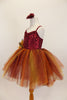 Rich earth-tone tutu dress has burgundy sequined bodice. Skirt is glitter ombré tulle over burgundy tulle layers with gold floral accent & hair accessory.  Left side