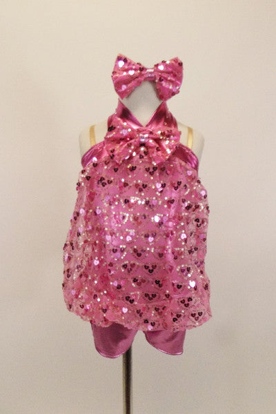 Heart sequin pink blouson top is attached to a metallic pink biketard with metallic yolk & halter straps. Has large sequined bow tie & matching hair accessory. Front