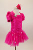 Hot pink stretch satin ruched dress has attached bolero with crystal accents,a  tulle skirt with silver polka dots & pouf sleeves. Comes with hair accessory. Right side