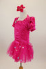 Hot pink stretch satin ruched dress has attached bolero with crystal accents,a  tulle skirt with silver polka dots & pouf sleeves. Comes with hair accessory. Left side