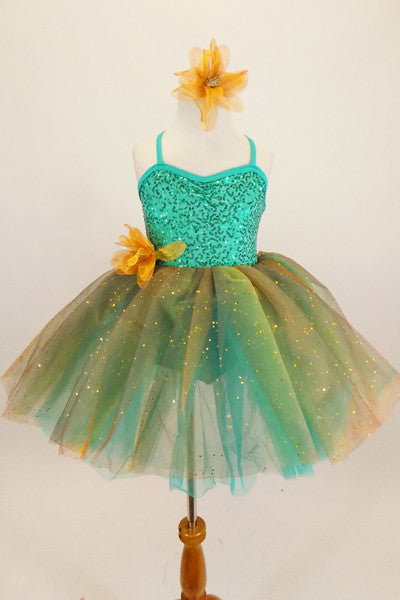 Aqua  jewel-tone tutu dress has sequin spandex front with cross straps. Skirt is glitter ombré tulle & soft aqua  beneath. Has gold flower at waist & for hair. Front