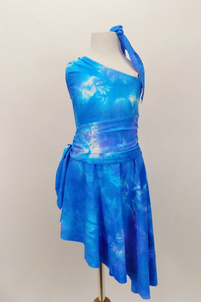 Asymmetrical tank style dress has tie-dye pattern in shade of blues. Sides of the dress are gathered with ties for better fit. Comes with matching hair tie. Front