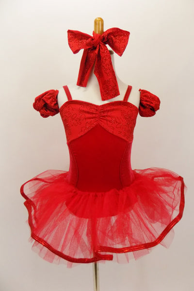 Red princess-cut camisole leotard has floral pattern bust area and matching arm poufs. There is a red pull-on tutu skirt with ribbon edging & matching hair bow. Front