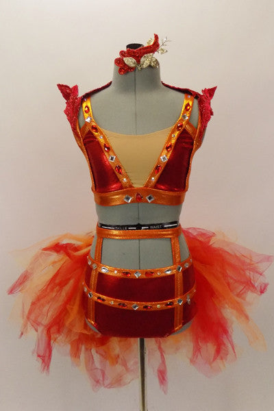 Two-piece costume is red metallic base with cage-like orange trim & accents  covered with crystals and jewels. Back bustle is multiple layers fiery tulle. Front