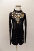 Long sleeved black biketard has high collar, low open back with 3 straps& crystals. Sleeves have silver zig-zag pattern and large jeweled bib. Has hair clip. Front