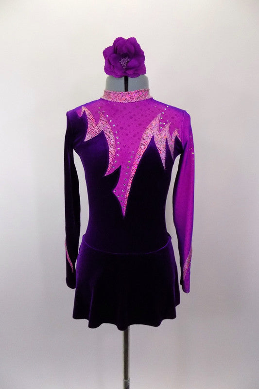 Unique purple velvet skater's dress has intricate pink spike design on bodice front and back with crystal accents & keyhole back. Sleeves are alternate color of purple-pink . Comes with floral hair accessory. Front