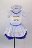 White sailor dress has princess cut seams, pouf sleeves and gold sailor buttons and hand painted anchor design over blue lace petticoat. Comes with sailor hat. Front