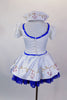 White sailor dress has princess cut seams, pouf sleeves and gold sailor buttons and hand painted anchor design over blue lace petticoat. Comes with sailor hat. Back
