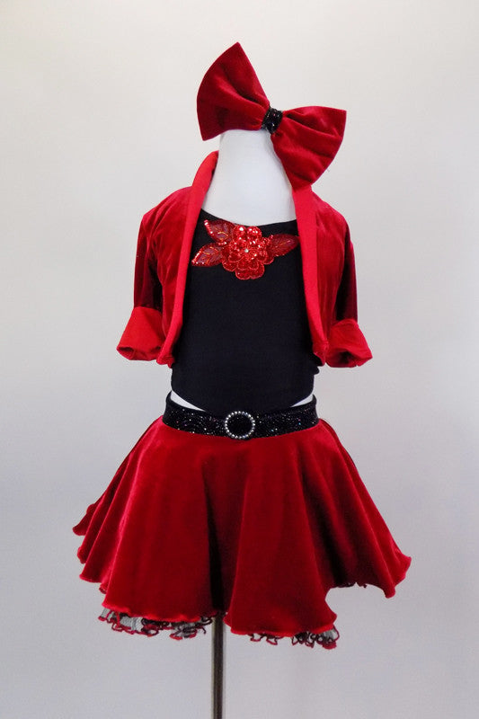 Red velvet skirt has ruffled black petticoat & crystaled waistband. Has red velvet short jacket over black crop-top with sequin accent. Has red velvet hair bow. Front