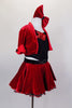 Red velvet skirt has ruffled black petticoat & crystaled waistband. Has red velvet short jacket over black crop-top with sequin accent. Has red velvet hair bow. Right side