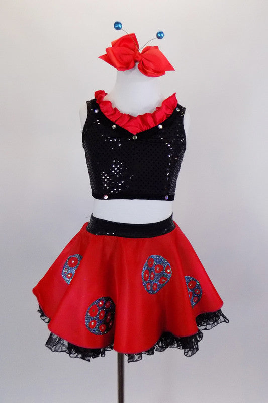 Ladybug themed costume has red skirt with large crystaled blue dots over layers of black lace petticoat. Comes with black sequin top & matching hair accessory. Front