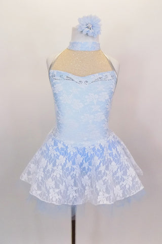 White lace over pale blue base leotard dress has a high neck & open back. Front bust is nude sheer with silver swirls. Has silver piping & blue tulle petticoat. Comes with matching hair flower. Front