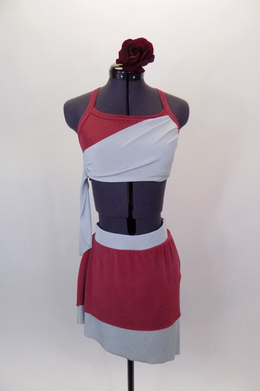 Deep rose and pale grey two-piece costume has halter neck bra with angled back straps. The matching knee length skirt is soft flowing stretch. Comes with matching  hair accessory. Front
