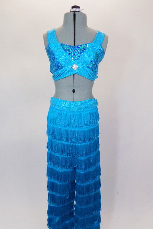 2-piece costume has layers of fringe covered pants in deepening shades of turquoise. Sequined half-top has bands that cross over the front with jewel accent. Comes with crystal hair barrette. Front