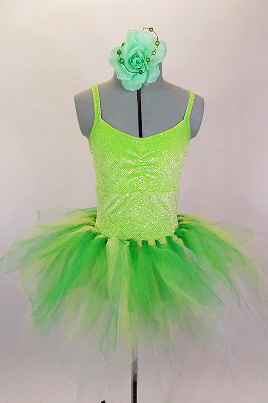 Green 2-piece costume is comprised of a neon green sparkle camisole leotard base. The pull on tutu is hand knotted strands of green yellow and white tulle. Comes with green floral hair accessory. Front