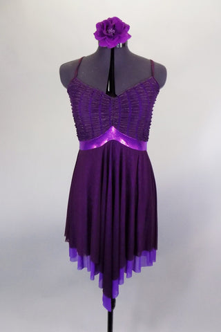 Eggplant dress has leotard base with cross straps & fine pleated gold-flecked bodice with pinch front. Dress has purple metallic band below the empire waist. Comes with floral hair accessory. Front