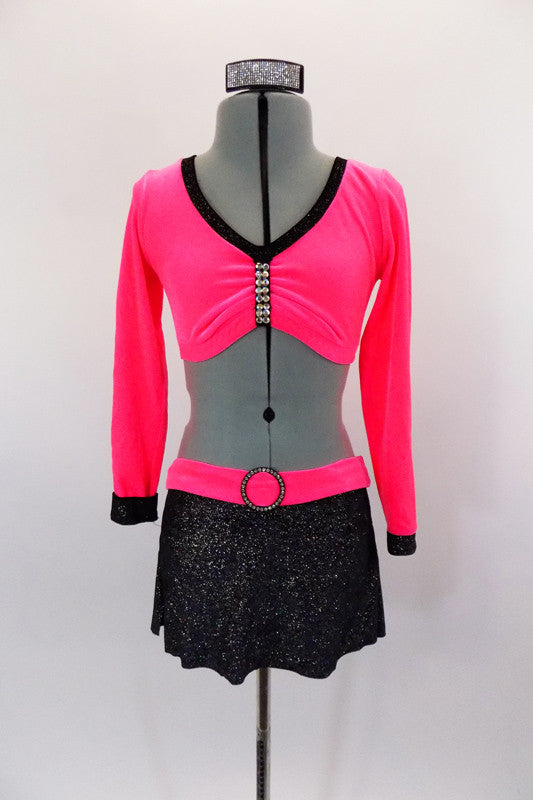 Neon pink velvet, long sleeved half top has crystalled pinch front. The black sparkle skirt has attached panty & pink velvet waistband with crystal buckle. Comes with hair accessory. Front