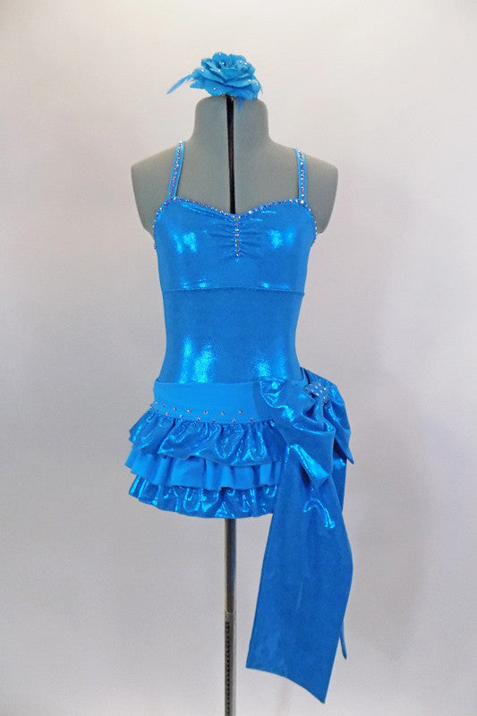 Turquoise metallic leotard has cross straps & edging completely covered with crystals. Separate pull-on skirt has layers of ruffles & large crystaled bow. Comes with matching hair accessory. Front