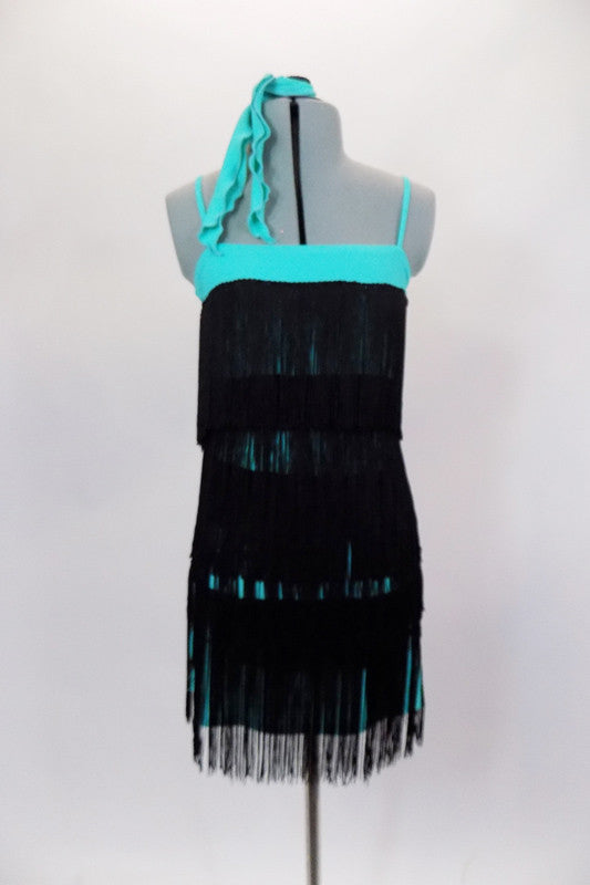 Turquoise stretch camisole flapper dress has layers of black fringe. The dress has a separate black panty  and matching hair tie. Front