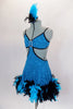 Turquoise sequined dress has feather trim at skirt bottom. Sides are completely open with large crystal buckle accent at bust. Comes with feather hair accessory. Side
