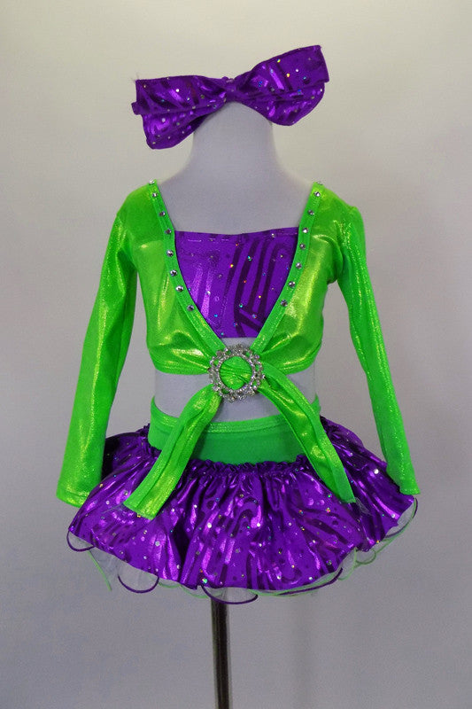 2- piece costume has purple glitter ruffle skirt with large green back bow and layers of white curly hem petticoat. Long sleeved green top has purple center. Comes with crystal buckle accent and purple hair bow. Front