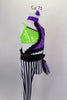 Black & white striped unitard has one long & one short leg with purple & black hip bustle. It's attached to purple lace asymmetrical shrug with green bra below. Comes with hair accessory. Right side