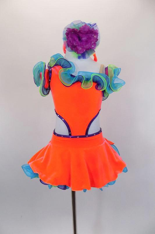 Bright orange velvet one-shoulder dress has open sides with purple crystals. Curly hem ruffles in lime, turquoise & purple accent the neckline & petticoat edge. Comes with ruffled gauntlets and floral headband. Front