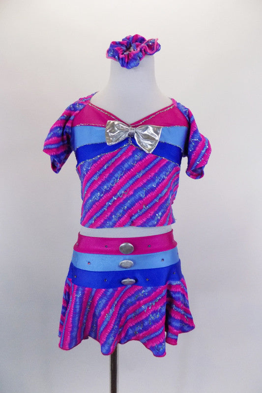 2-piece, purple-pink stripe costume with silver fleck, has pouf sleeve top. Bust and waist have bands of periwinkle-blue-pink, & silver bow. Has matching skort. Comes with matching hair scrunchie. Front