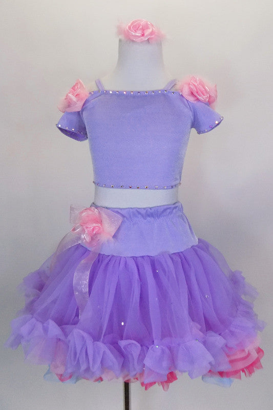 Pale lavender costume has shoulder cap sleeved top edged with crystal & satin roses along shoulder. Skirt has layers of pastel ruffles & satin rose hip accent. Comes with rose hair accessory. Front