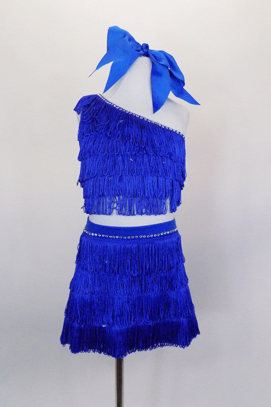 2- piece electric blue costume has single shoulder half top covered in layers of blue fringe & crystal accents. Comes with matching fringe skirt and hair bow. Front