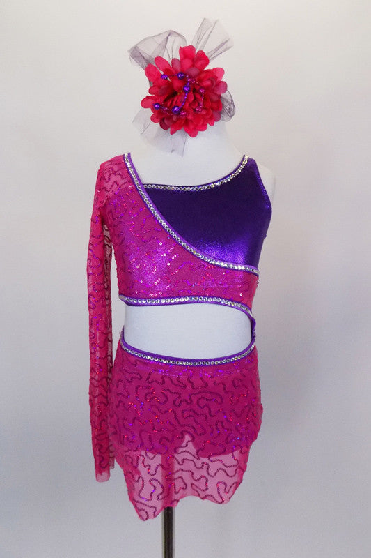 Asymmetrical, 2-piece costume, has a fuchsia pink sequined mesh skirt joined at hip to one shoulder open half top. Beneath is purple opposite shoulder bra.  Comes with floral hair accessory. Front