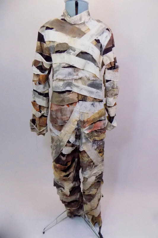 Full length long sleeved coverall  is comprised entirely of strips of ragged bandage like fabric in whites, creams and browns. Comes with mummy hat accessory. Front