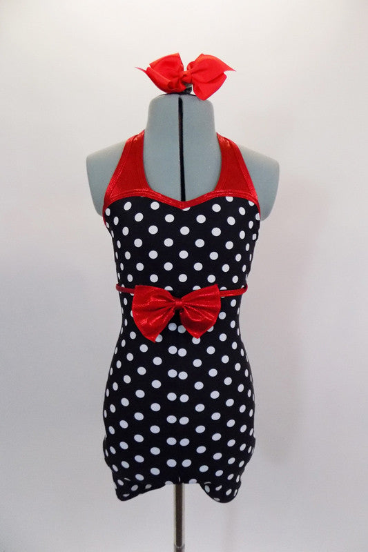 Black and white polka dot short unitard has red metallic banding and halter neck. The waist has a large red metallic bow. Comes with red bow hair accessory. Front
