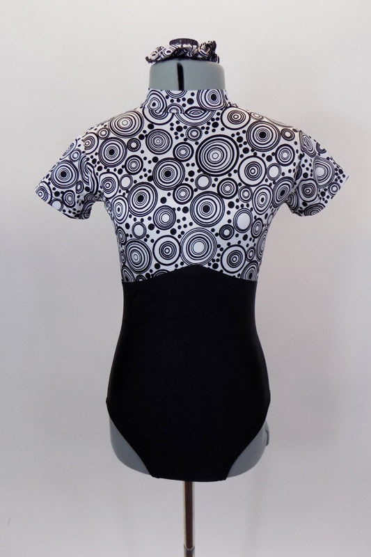 Black and white circular kaleidoscope pattern leotard has black bottom, cap sleeves and high neck with keyhole back. Comes with matching hair accessory. Front
