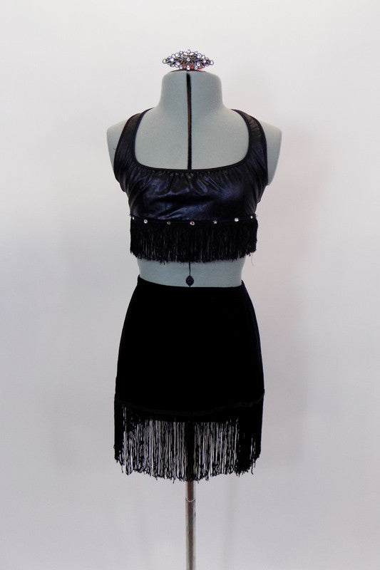 Black faux leather halter bralette is lined at with crystals & black fringe. Matching black velvet pull-on skirt has black fringe edge & has a separate panty. Comes with hair accessory. Front