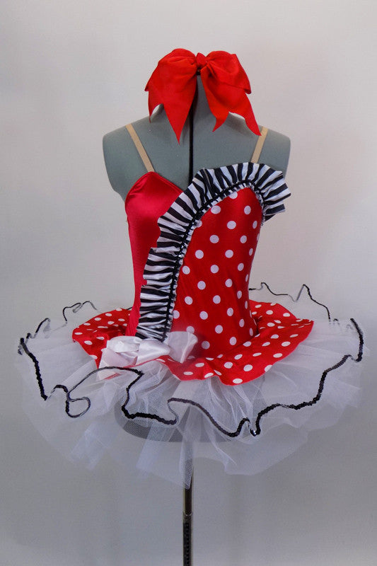 Red & white polka dot tutu dress has white tutu base with black sequin edge. Has black & white striped ruffle across sweetheart bodice. Comes with hair bow. Front