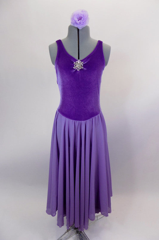 Lavender velvet leotard dress has  pinch front, crystal brooch & low back. Layers of flowing lavender chiffon that make up the knee length skirt.  Comes with lavender floral hair accessory. Front