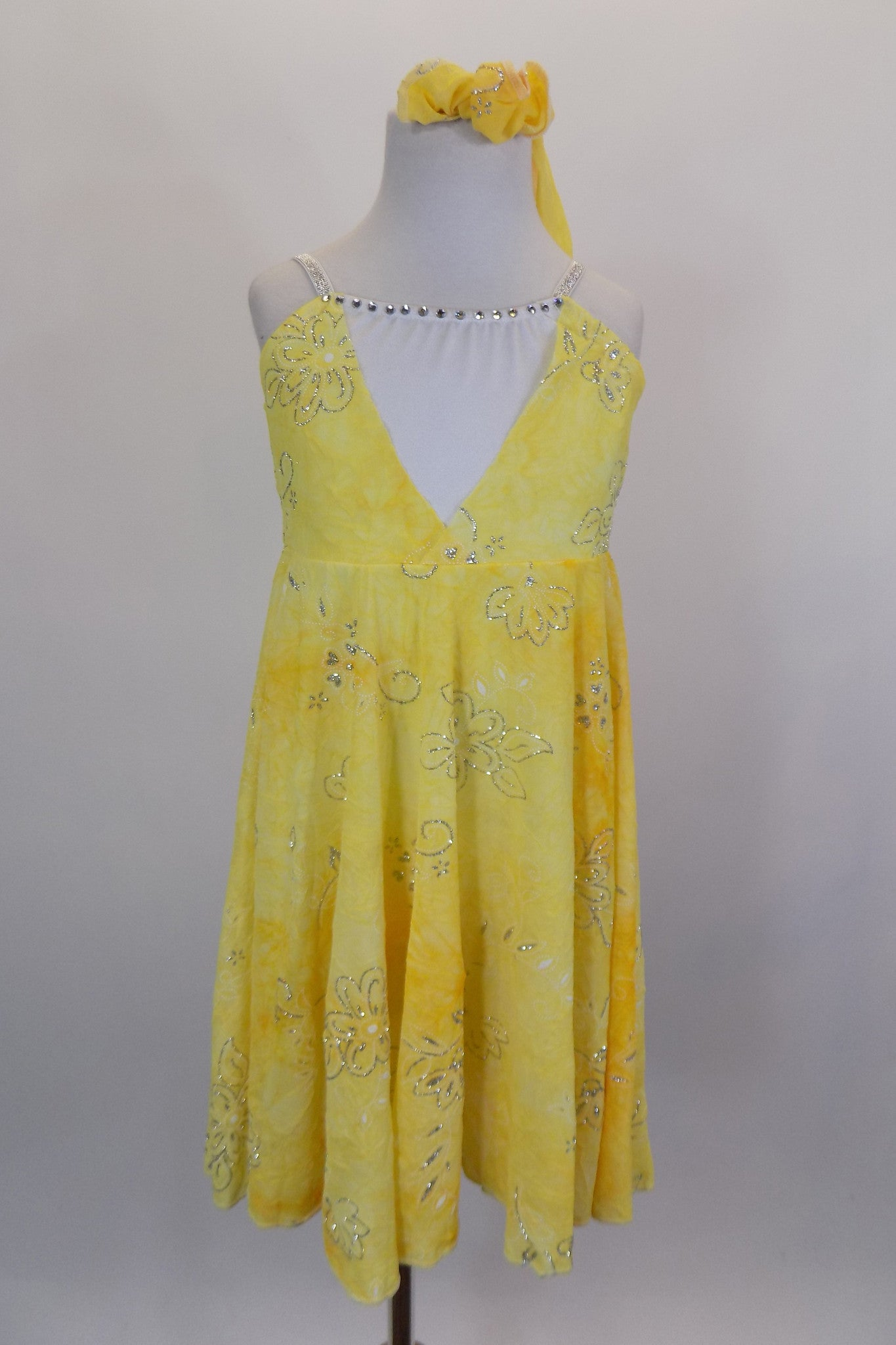 Yellow mesh lyrical dress with silver swirl designs has low deep V front with white crystaled center & crystaled straps. Comes with matching hair accessory. Front