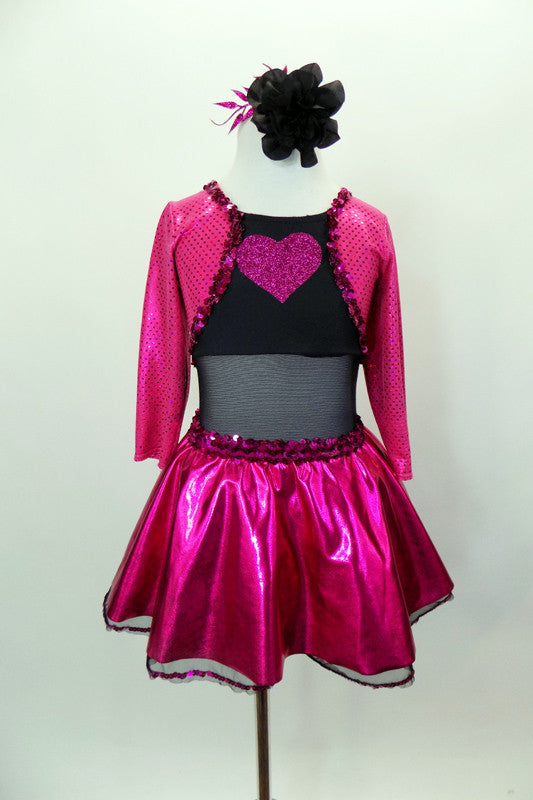 Black leotard has black sheer mesh midriff & black bottom. Has pink glitter skirt &  ¾ sleeved attached jacket style top has pink glitter heart on black bust. Comes with hair accessory. Front